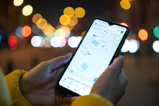 Ivano-Frankivsk, Ukraine - November 7, 2020: Close up of female hands holding mobile phone with Google maps navigation application at night city street.