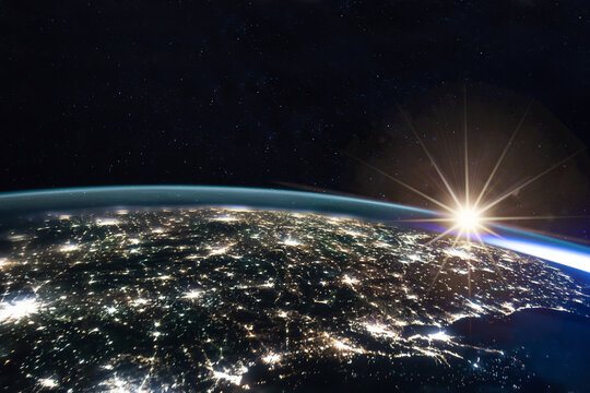 Composite image of the sun rising on earth view from space with the lights of the cities at night. Human activities, greenhouse gas emissions concept. Elements of this image are furnished by NASA