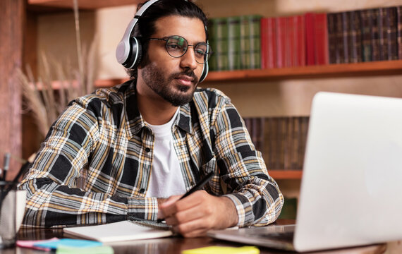 Arab Student Guy Learning Online At Laptop Sitting In Library