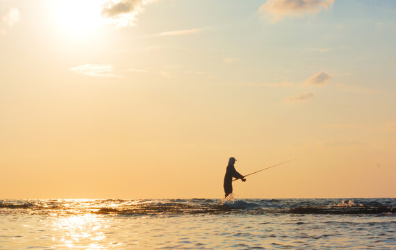 A silhouette of fisherman with fishing rod standing at shallow water in the middle of the sea and fishing at evening hour