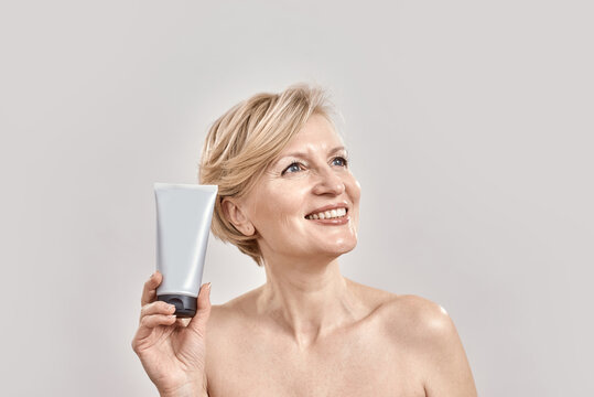 Beautiful middle aged woman smiling aside, holding, advertising cosmetic skincare bodycare product while posing isolated over grey background