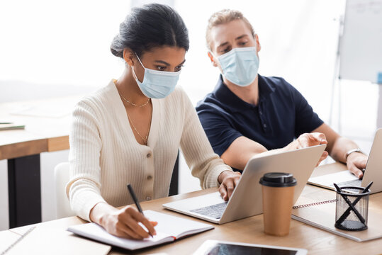 african american businesswoman typing on laptop an writing in notebook near colleague in medical mask on blurred background