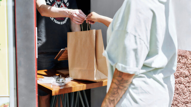 Cropped shot of woman taking paper bag with her order from hands of shop assistant while collecting her purchase from the pickup point