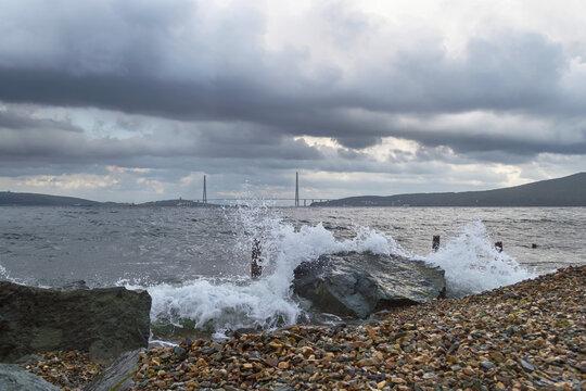splashing sea waves with Russkiy bridge on background