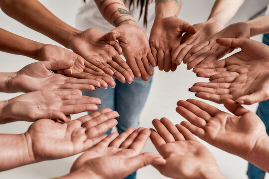 Diverse women holding their hands open palm together, making a circle over grey background. Concept of support, racial unity and relations in society
