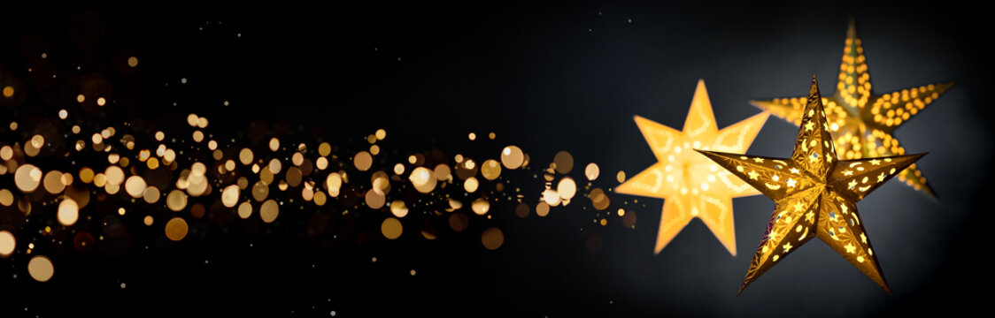 Ornamental gold star lanterns for Christmas on black background with golden bokeh stardust, extra wide format