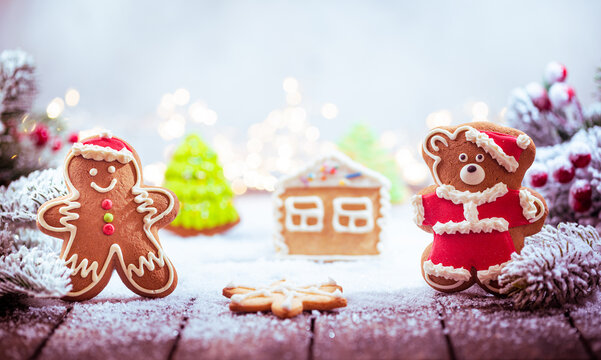 Christmas decorations on snow with gingerbread men, fir tree branches and christmas lights. Winter Decoration Background with copy space for text