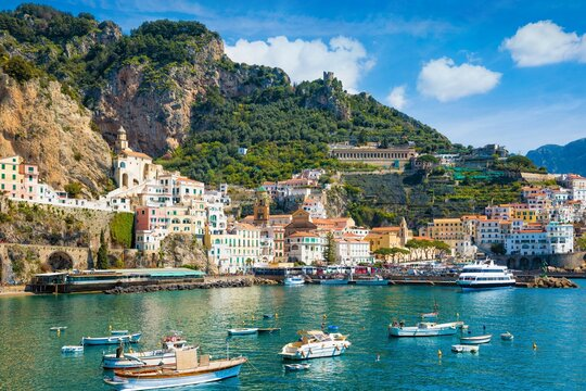 Beautiful Amalfi with hotels on hills leading down to coast, comfortable beaches and azure sea in Campania, Italy.