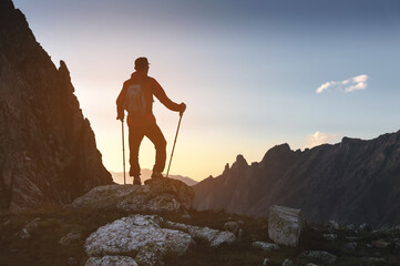 A silhouette of a man in a cap with sunglasses and a backpack stands high in the mountains on top of a stone with trekking poles high in the mountains at sunset at dusk in the evening