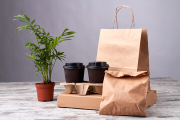 Fototapeta Coffee cardboard cups and paper packages. Eko friendly packing on the wooden table. Beautiful plant in flowerpot.