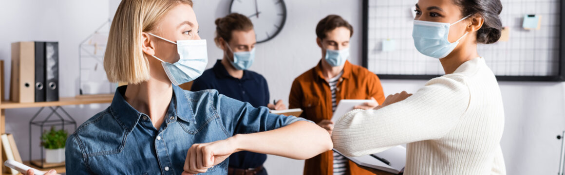 young businesswomen in medical masks doing elbow bump near colleagues on blurred background, banner