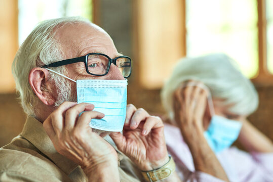 Two pensioners are putting on protective masks