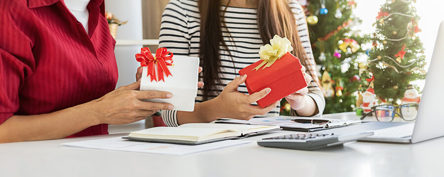 Business woman exchanging a present in office on last working day. Young creative people are celebrating holiday in modern office. Merry Christmas and Happy New Year.