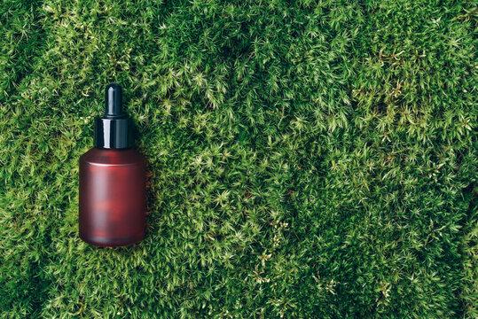Red matt glass cosmetic bottle on green background, natural moss, grass. Skin care, organic body treatment, spa concept. Vegan eco friendly cosmetology product. Biophilia design. Organic cosmetics