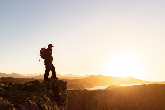 Side view of anonymous male hiker with backpack standing on rock in mountains and enjoying amazing sundown during vacation