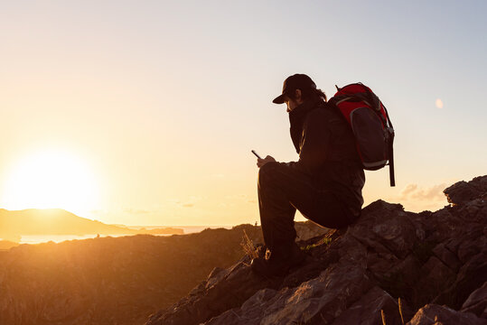 Side view of unrecognizable male hiker sitting on rock in highlands and browsing cellphone while admiring sunset