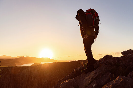 Side view of unrecognizable male traveler with backpack standing on hill and admiring scenery of mountain ridge under sunset sky