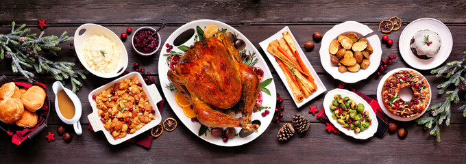 Traditional Christmas turkey dinner. Top view panoramic table scene on a dark wood banner...