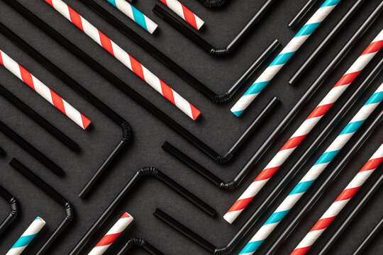 Top view flat lay composition with black and withe and red plastic straws for takeaway drinks arranged in geometric ornament on black background
