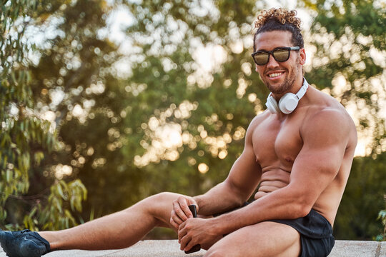 Muscular male athlete with strong body and headphones relaxing on bench during workout in park while smiling and looking at camera