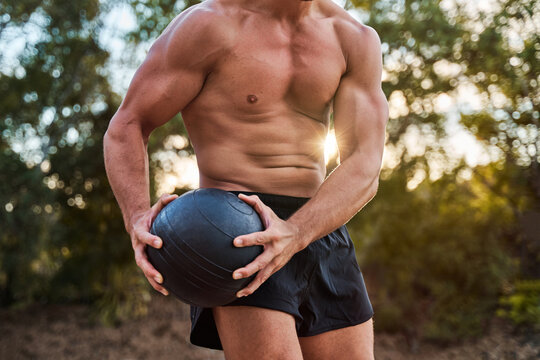 Crop unrecognizable male athlete with muscular body doing exercises with medicine ball during workout in park in summer