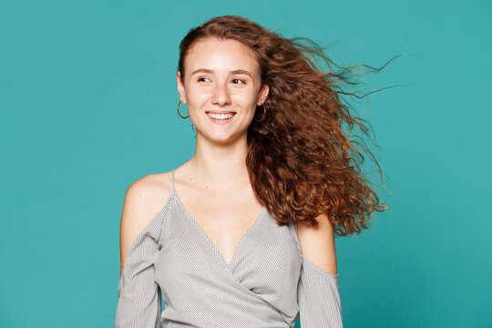 Calm female model in casual wear and with long hair standing on blue background in studio and looking away