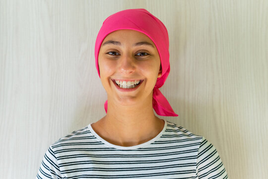 Young delighted female with cancer wearing headscarf standing in apartment and looking at camera