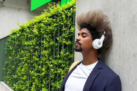 Black man with afro hair leaning against a wall with his eyes closed while listening to music with a wireless headset on the street