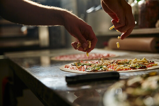 Process of preparation pizza with various vegetables on marble counter with ingredients and utensils in pizzeria kitchen