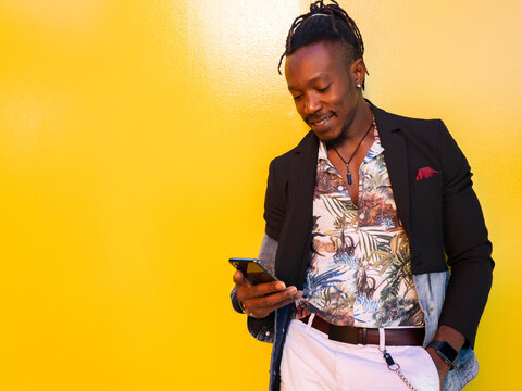 Smiling African American entrepreneur in fancy clothes standing near yellow wall in city and browsing cellphone while working remotely