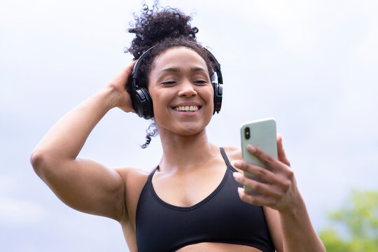Delighted black female athlete in sports bra standing in city and enjoying songs with closed eyes in wireless headphones during training