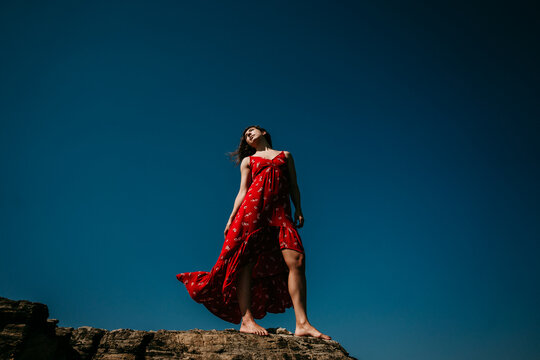 From below low angle of barefoot female in long red dress standing with eyes closed on rough hill