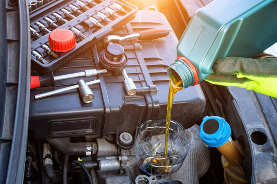 Pouring oil to car engine. Fresh oil poured during an oil change to a car. Refueling and pouring oil quality into the engine motor car Transmission and Maintenance Gear. Energy fuel concept.