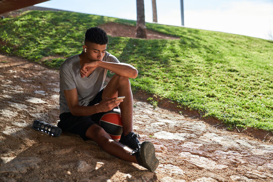 Young ethnic male athlete in sportswear with ball and bottle of water listening to music with earbuds and browsing smartphone while resting during workout in park