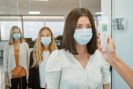 Receptionist with thermometer gun checking body temperature of coworkers before entering office space during coronavirus pandemic