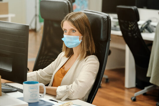 Focused young female office employee in protective mask using computer while working at table in contemporary workplace during coronavirus pandemic