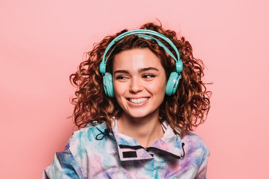 Studio portrait of curly redhead girl smiling at camera over pink background. She is wearing green headphones.