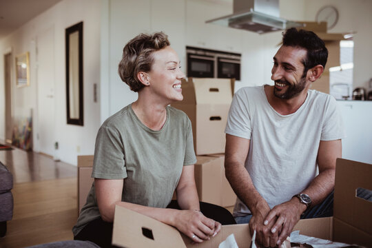 Smiling male and female partners looking at each other while unpacking cardboard boxes in new house