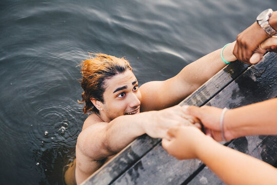 Cropped image of male friends holding hands with young man in lake