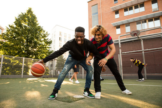 Male friends with playing basketball in sports field