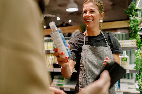 Smiling saleswoman assisting male customer in supermarket
