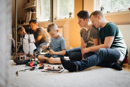 Homosexual fathers looking at son playing while making toy boat at home