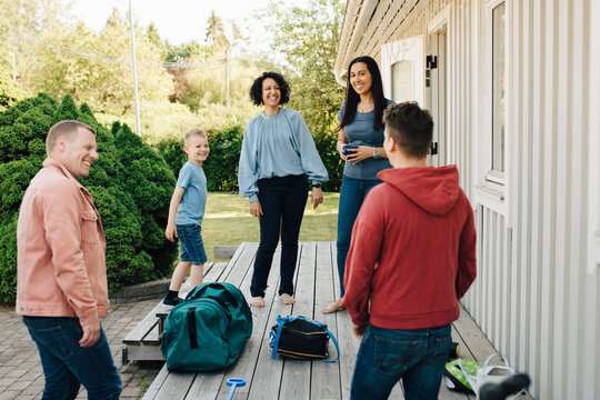 Smiling mothers and son looking at gay couple standing by patio during weekend