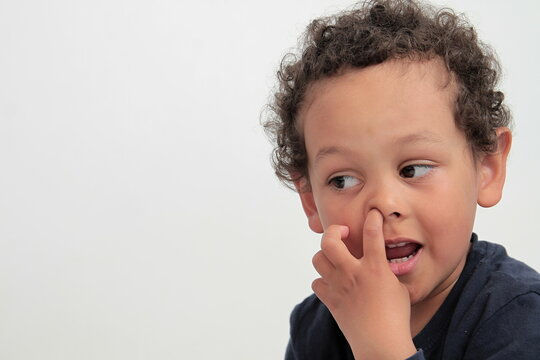 little boy picking his nose on white background stock photo