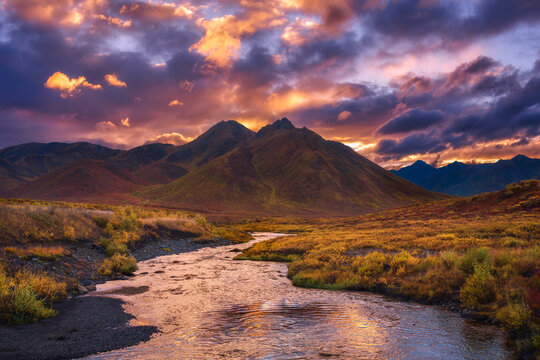 Scenic view of Ogilvie Mountains with stream in foreground during sunset