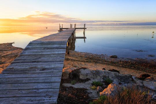 View of wooden pier on beach during sunrise