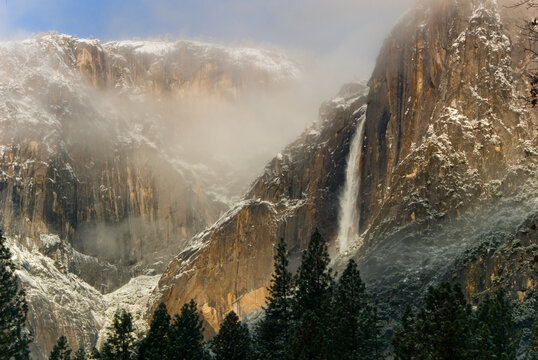 Scenic view of waterfall and mountains in fog