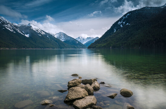 Scenic view of lake with mountains against cloudy sky