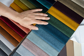 A woman's hand lies on a catalog of fabrics of different colors, a woman chooses a fabric for new upholstered furniture at home, and she will give old furniture to the poor