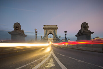 View of light trail on Szechenyi Chain Bridge with city in background Fotomurales